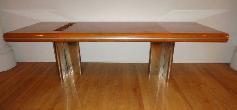 Desk by Hans von Klier in walnut wood with three drawers, a center leather writing section, and a inset storage space which includes two sliding walnut supply holders. The desk has a strip of inset, polished metal along its curved apron and is