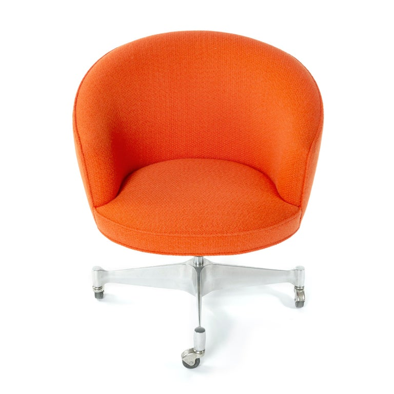 A George Nelson designed rolling desk chair with orange fabric supported by a swivel base with casters. Manufactured by George Nelson and Associates in the 1960s. Newly reupholstered.