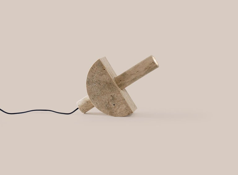 In this easily adjustable, solid travertine Exhale the Void table lamp by the Australian design studio Addition Studios, the pieces slide together and then rotate easily along the arc of the semi-circle, so that users can direct the light to suit