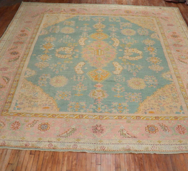 """A colorful antique early 20th century Turkish Oushak rug. The field is teal; the border is pink. The rug has a lot of character and exhilarating in person  Measures: 13'4"""" x 15'8""""  Antique Turkish Oushak rugs have been woven in Western Turkey"""