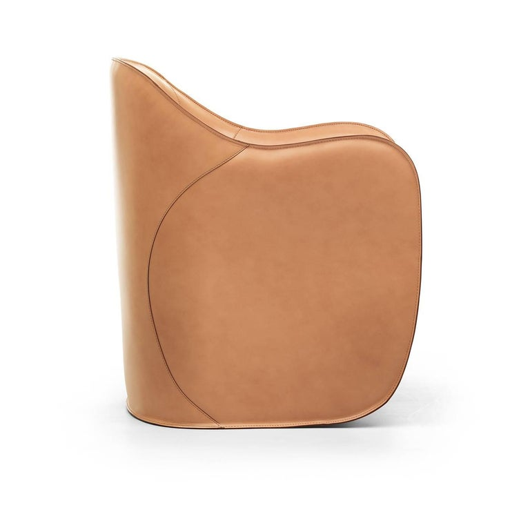 Designed by Alberto Colzani in 2013, this set of armchair and ottoman will add sophistication and a pop of color to a modern living room or study. The polyurethane core creates the sinuous, enveloping shape of the chair, that is mirrored in the