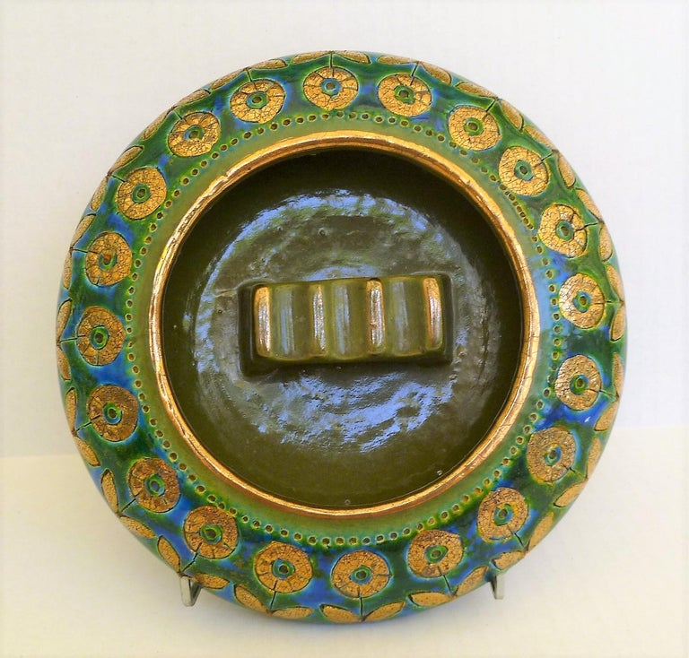 1960s exotic Mid-Century Modern ashtray by Aldo Londi for Rosenthal Netter and produced by Bitossi. Wonderful blue and gold flower sgraffito pattern, named Thai Silk, over an earth green glaze. Large enough to be use as a cigar ashtray. In Very good