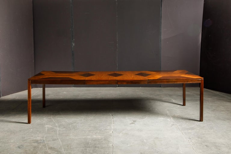 This beautifully refinished 1970's Parsons dining table by Milo Baughman for Directional features strips of highly grained exotic woods in various finishes and patterns creating contrasting lines and shaped for a spectacular effect.   In excellent