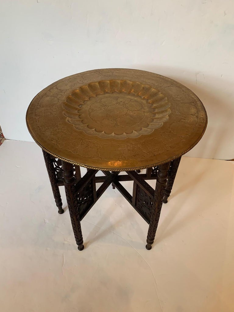 Exotic Moroccan tray top end table having beautiful etched brass tray with central recessed scalloped circle and folding intricately carved base. Brass has nice aged patina and matte finish.