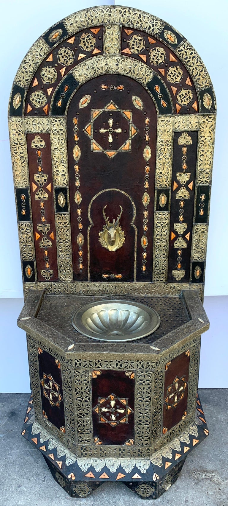 Exotic vintage Moroccan brass, bone, and silvered fountain, standing 6 feet tall the demilune backsplash profusely inlaid and mounted with various decorative elements, with a central brass stag fountain spilling into a 15-Inch diameter ribbed bowl