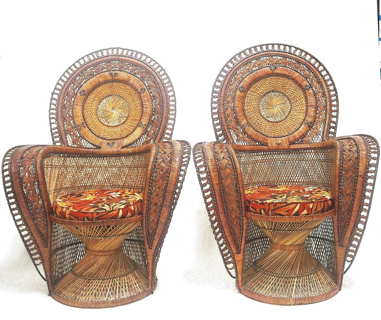 Early to mid-20th century pair of dramatic medallion back   peacock chairs from a Palm Beach mansion.       Hollywood glamour exudes in a Classic pair of regal throne wicker rattan peacock chairs with highly detailed medallion circular inset fan