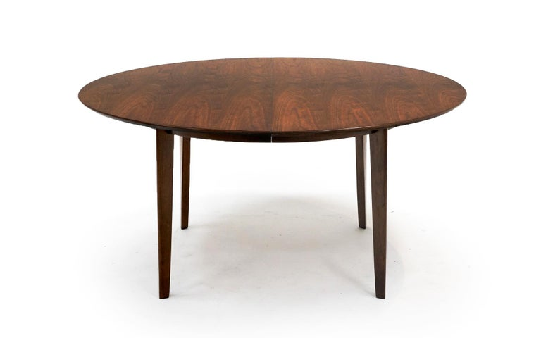 Walnut, almost round, dining table with two leaves designed by Edward Wormley for Dunbar. Heavy duty construction. Original finish with only very light signs of wear.  Width without leaves is 60 inches. Each leaf is 14 inches wide. Total width with