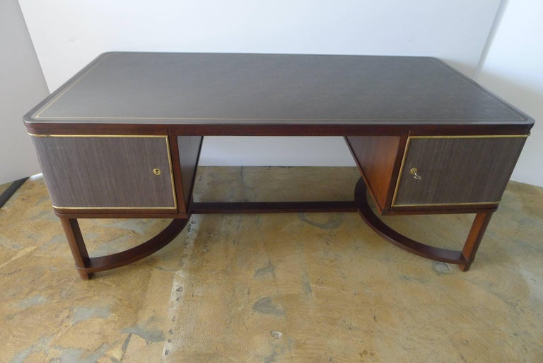 Restored expansive Art Deco French executive desk. Updated with a modern interpretation. Restored walnut veneer, new leather top with gold embossed details, restored brass, grass cloth panels. Two doors with interior shelving. Beautiful, excellent