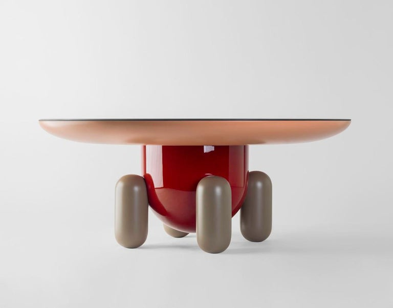 Laquered fibreglass body. Solid turned wooden legs and lacquered. Painted glass tabletop.