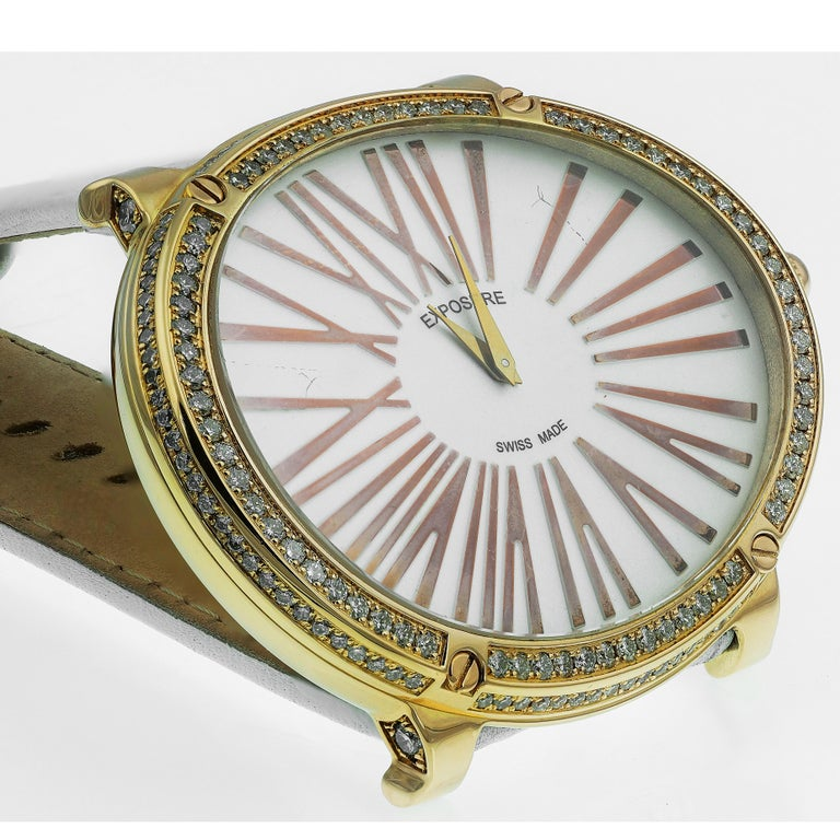 Stunning Exposure watch with a white diald, bold large roman numerals in gold with quartz movement. A thick oval gold border embedded with glistening round brilliant cut diamonds. The wide white leather straps compliment the glow of the gold and has