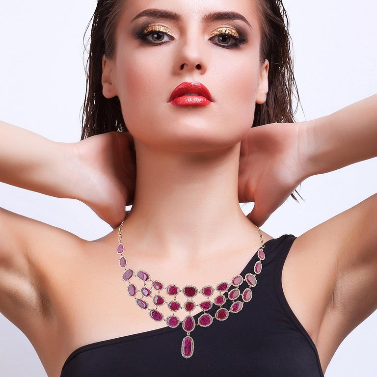Crafted from 18-karat gold, this exquisite necklace is set with 59.59 carats of natural rubies and 6.64-carats of glimmering diamonds.  The tiered choker style makes a great statement piece. Instock  Please note that carat weights may slightly vary