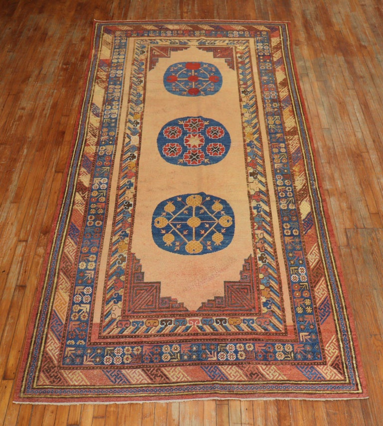 Early 20th century colorful antique Khotan gallery rug. The field is a bone color, denim blue, rust accents are dominant. 