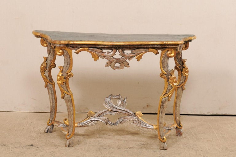 An Italian carved and gilded console table with faux marble top from the 19th century. This antique console table from Italy features a faux-marbled top, nicely carved and pierced skirt, and raised upon four curvaceous and slender legs, wrapped with