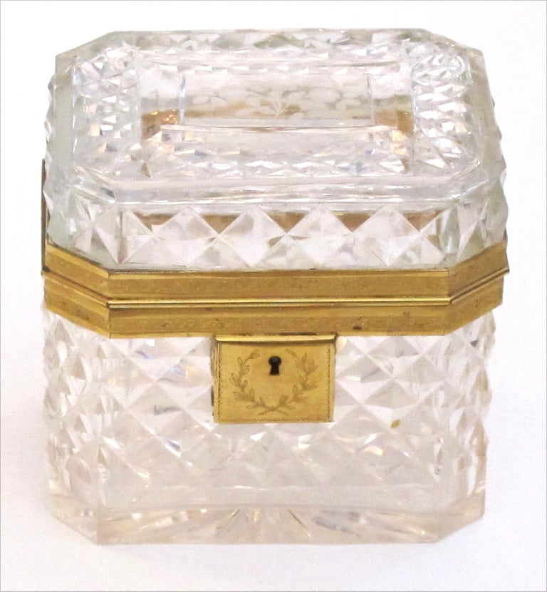 Of rectangular shape with canted corners this cut-crystal trinket box with a hinged lid; adorned overall with finely chased doré bronze mounts; a jewel of a box of first quality.