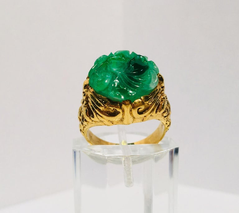 Beautifully detailed, estate, 22 karat heavy yellow gold ring features a bezel-set, variegated, apple green, richly carved, natural jade flower.  The gold work in the mounting includes deeply textured swirls and curlicues.    Jade flower measures
