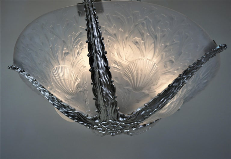 Exquisite chandelier with five clear frost color glass inserts and stylized sea coral and shell relief.