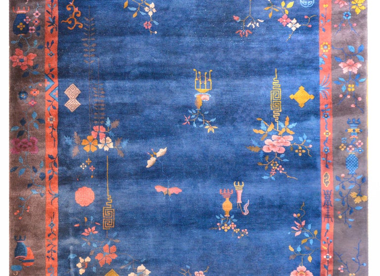 An exquisite Chinese Art Deco rug with an indigo field surrounded by a wide brown outer border with a thin orange inner border all overlaid with myriad auspicious flowering branches and planted pots with butterflies and other auspicious symbols