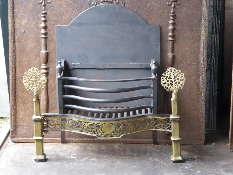 English Art Nouveau fireplace grate made of cast iron, wrought iron and polished brass. The total width of the front of the fireplace grate is 35 inch (89 cm).