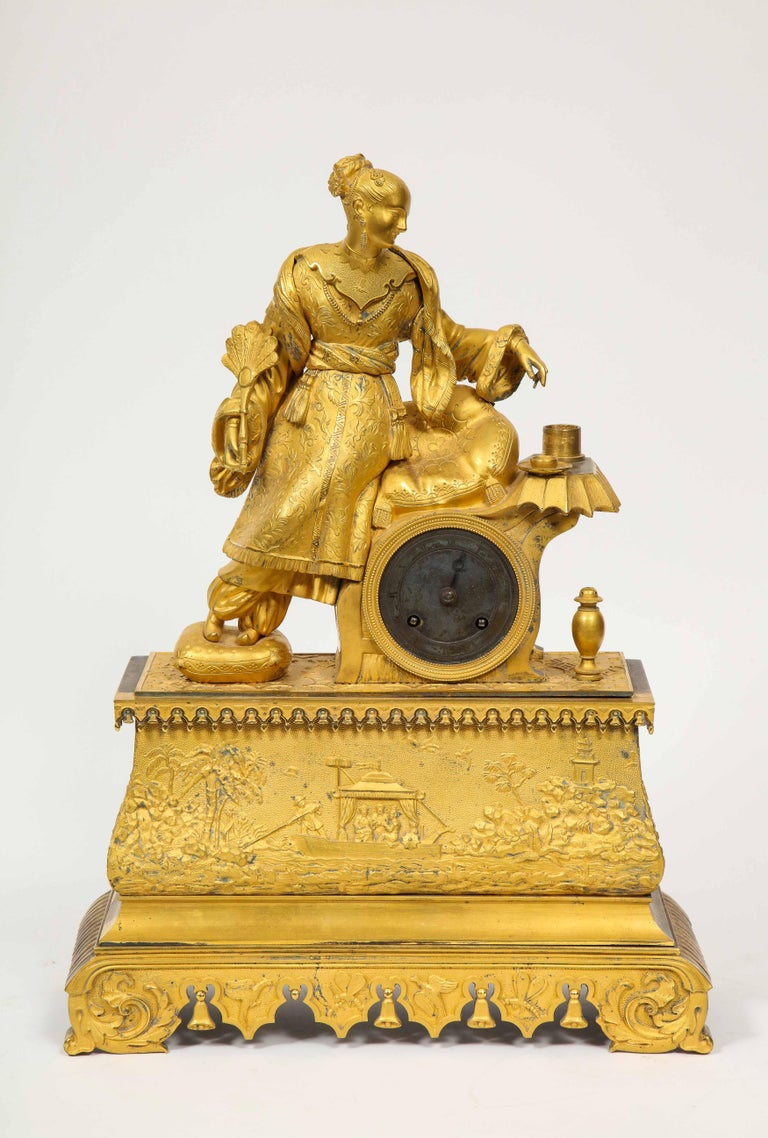 Exquisite French Charles X ormolu bronze chinoiserie figural table clock, early 19th century.  Depicting a Chinese woman wearing jewelry, dressed in her elaborate garments, holding a fan, resting on her saddle throne. The clock case depicting the