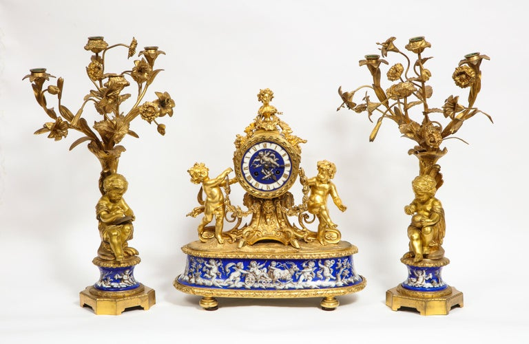 Exquisite French ormolu bronze and blue porcelain mounted three-piece clock garniture set, circa 1880.