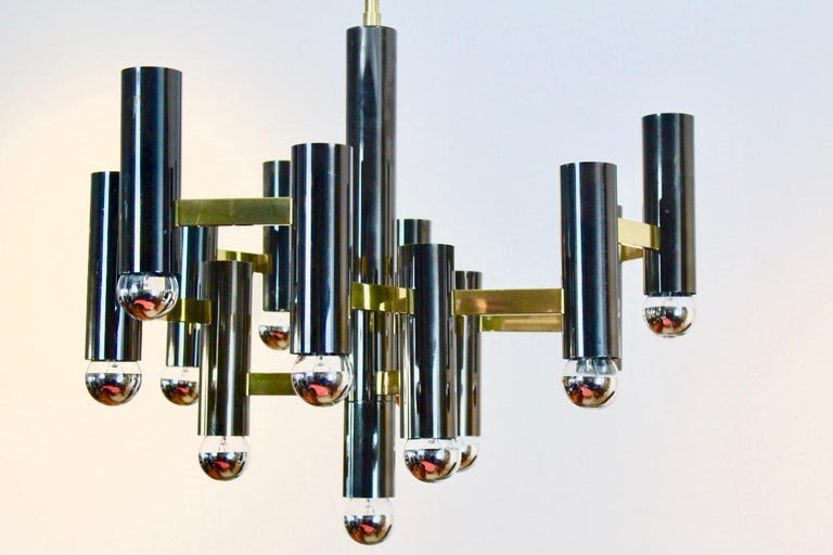 Very beautiful and rare Gaetano Sciolari chandelier in brass and the unique black pearl color. This is a large 13 bulbs chandelier hanging on a massive brass bar. Nice modernist geometric structure and with a perfect style and fantastic light