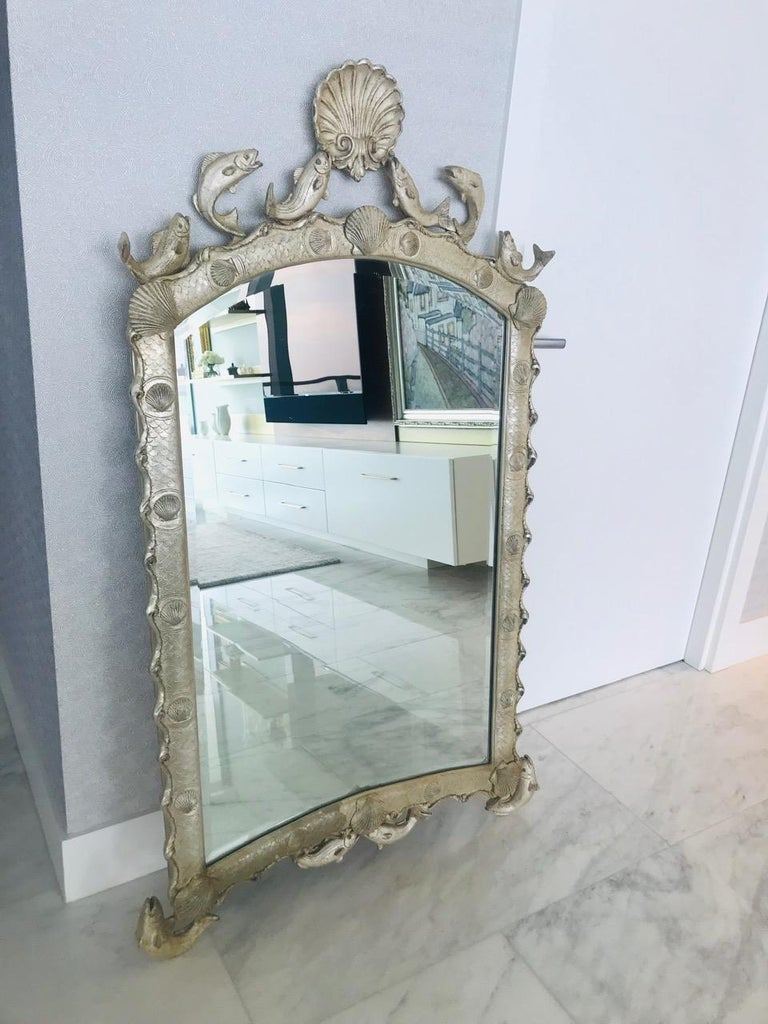 Stunning Venetian style scalloped mirror with ocean sea life theme. The mirror features an arched frame with scalloped borders and with hand laid sterling silver leaf finish. Hand made by artisans using casting technique of wood, resin, and wire to