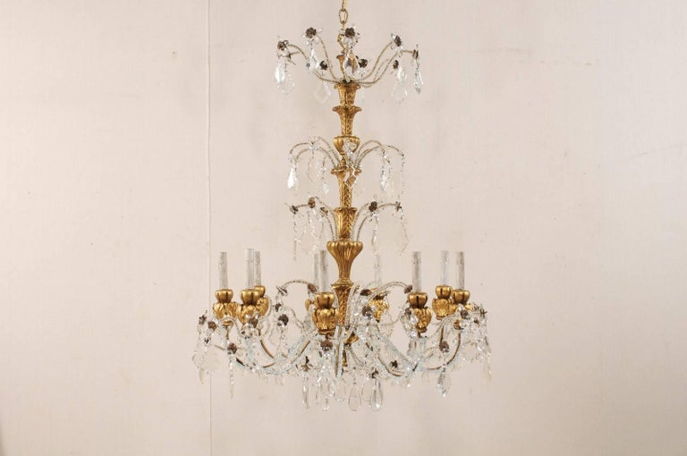 A vintage Italian nine-light crystal and wood chandelier. This Italian chandelier from the mid to late 20th century features a tall gilt, painted and beautifully carved wood central column, with a three-tiered crystal and Italian glass bead