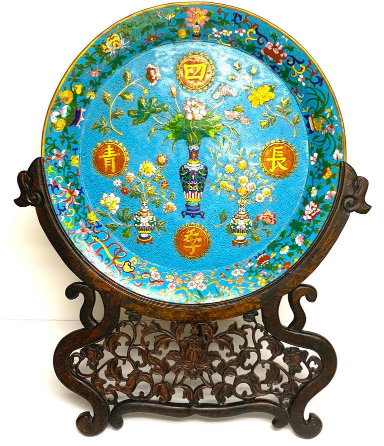 Exquisite Ming style Cloisonné charger and stand, profusely decorated front and back. The front with three dimensional (blown out/ raised) vases with flowers and four applied Chinese characters. The back vases and planters with Cherry blossoms and