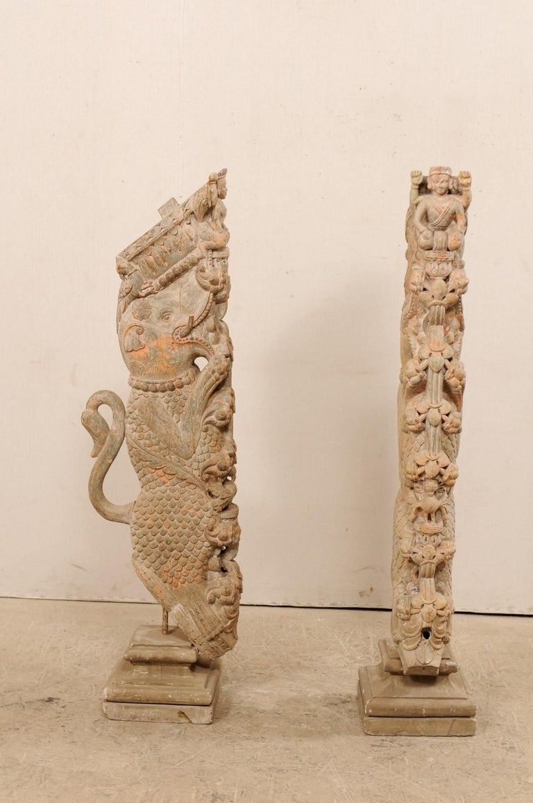 An exquisite pair of hand carved Hindu wooden temple struts, mounted on stone bases, from the 19th century. This pair of antique temple struts from S. India are magnificently carved with depiction of a scaled elephant kneeling serenely on a tower of