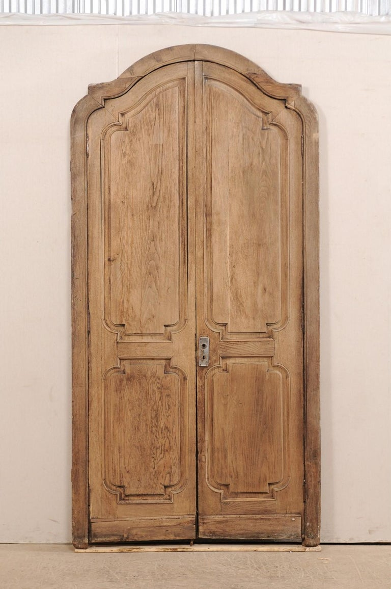 An exquisite pair of Spanish arched double doors with their original casing from the 19th century. This fabulous piece consists of two antique Spanish doors with their original casing. The surround or casing has a depressed arch pediment with eared