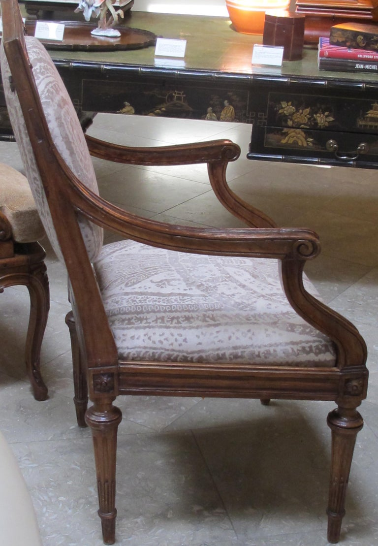 An exquisite and large-scaled pair of Italian neoclassical carved walnut upholstered arm chairs; each rectangular carved framed backrest with padded oval insert joining curved arms flanking a tight seat; all raised on graceful tapering supports;