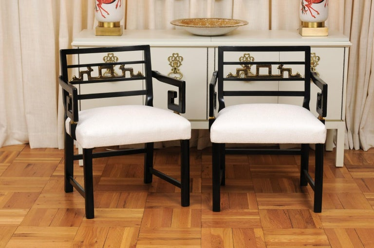 A stunning restored pair of modern chinoiserie style armchairs by Baker Furniture, circa 1960. Elegant, exceptionally constructed mahogany frame executed in black lacquer. Striking gold leaf inset back motif with stunning Greek Key arms. This rare
