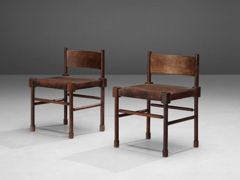 Side chairs, stained wood, patinated leather, Europe, 1940s  Rare side chairs with sculpted frame in stained wood and leather seats. What makes this design so unique is the way the designer played with proportions and shapes. The detailed carved