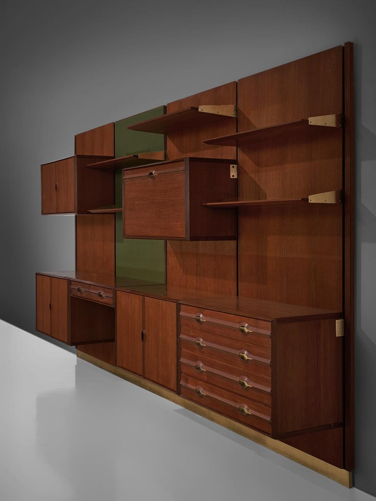 Cabinet by La Permanente Mobili Cantu, brass, teak, Italy, circa, 1955.  The monumental wall-mounted cabinet consists of four wall panels with various different storage facilities. The finish and details of this shelving wall unit are of a very