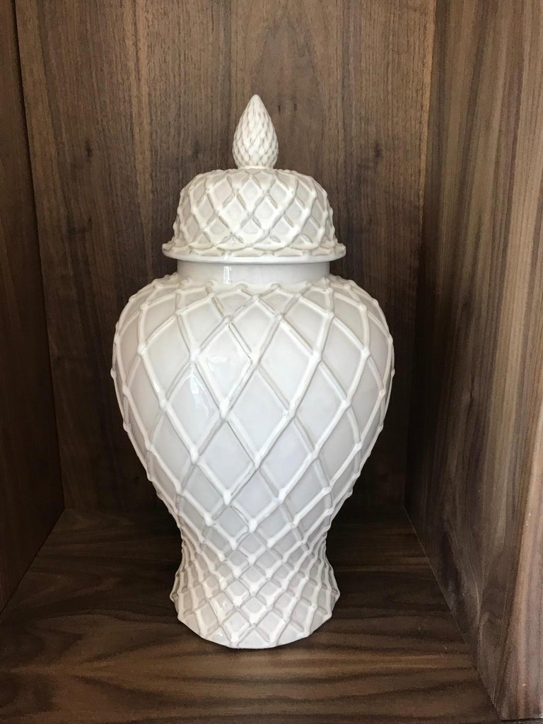 Hollywood Regency large pottery ginger jar with lid has gorgeous urn form with white glaze finish. Features both Chinese and Moorish inspired designs with lattice work throughout. Has tapered base and the lid features a stylized acorn finial or