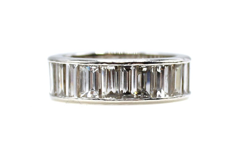 This exquisite beautifully hand-crafted eternity band is channel set with 32 bright white and sparkly baguette cut diamonds with an approximate total diamond weight of 8 carats. The baguettes measure over 6 millimeters in length, which is quite