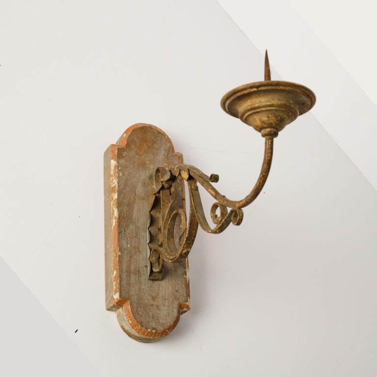 Exquisite wood and iron sconce with single arm. Beautiful original (or early paint) paint over gesso applied over surface of wooden back. Back is hand carved. Single forged iron arm decorated with hammered scrolling acanthus detail. Remnants of old