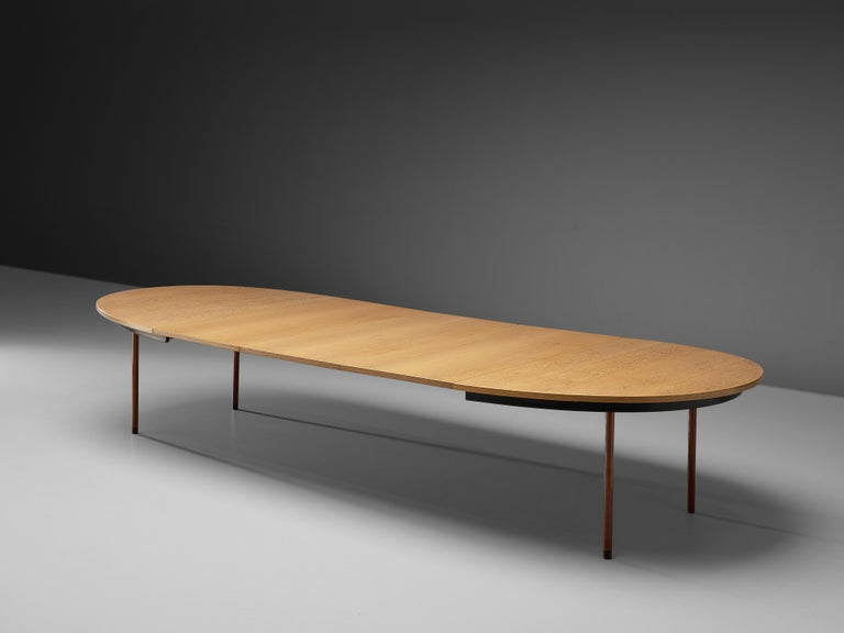 Extendable dining table, oak, red lacquered metal, Denmark, 1950s  Three extra leaves transform this dining table into an extra large table. The tabletop made out of oak is pulled apart to fit the three leaves in the middle. The small version