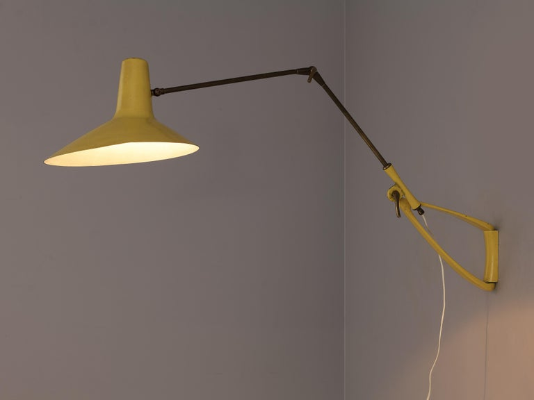 Wall light, yellow metal and brass, Italy, 1950s  This beautiful yellow lamp is executed in lacquered metal and solid brass. The key to the beauty of this lamp is in the open triangle detail of the arm and the delicate shape of the shade. The brass
