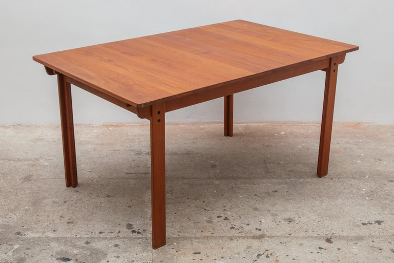 Vintage midcentury dining table made of solid teak in excellent condition. Can be easily extended with a leaf on each side.  Dimension table: 90 W x 72.5 H x 141 D cm, leaf: 90 W x 50 D cm.