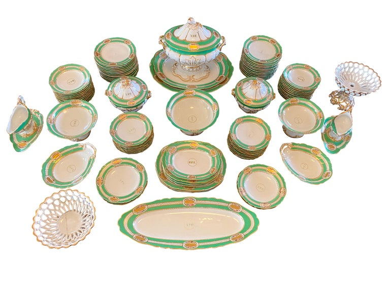Green borders with small floral cartouches, some painted monograms. Comprising 2 oval bowls. 9.13 W x 11 D x 2.75 H 2 gravy boats. With tray. 10.75 W x 6.63 D x 6 H centerpiece bowl. 11.5 diameter x 5.63 height 26 dinner plates. 9.13 diameter, 19