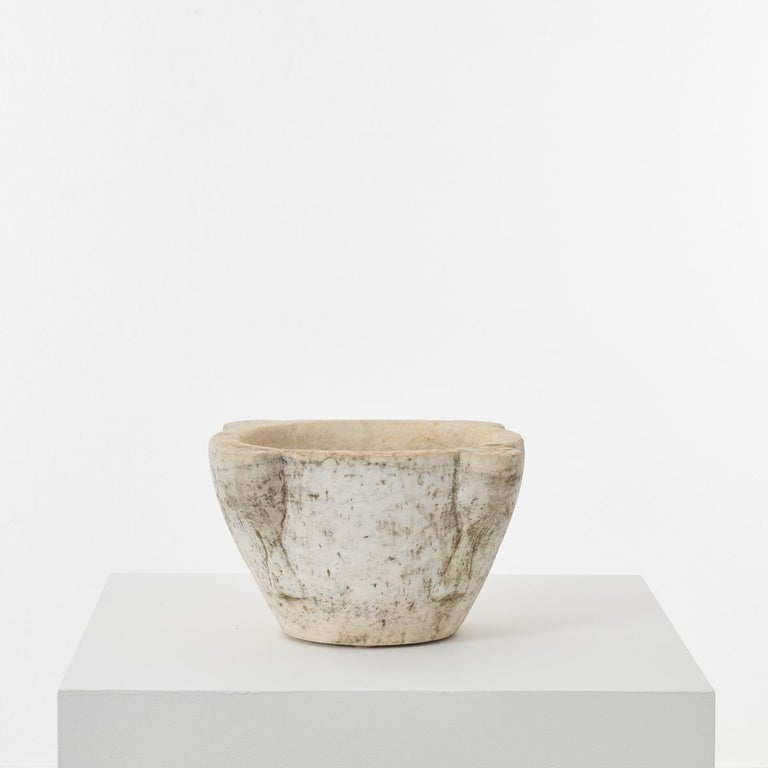 This ancient marble mortar has a rather mysterious aura about it. It is hand-sculpted from a single piece of stone, with beautiful ageing over time. Perhaps the most distinctive element of this piece is the chisel marks apparent on close inspection.