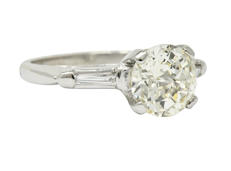 Centering a basket set jubilee cut round diamond weighing 1.72 carat; N color with VVS2 clarity  Flanked by two bar set tapered baguette cut diamonds weighing approximately 0.10 carat; eye-clean and white  Mounting is stamped for platinum, circa