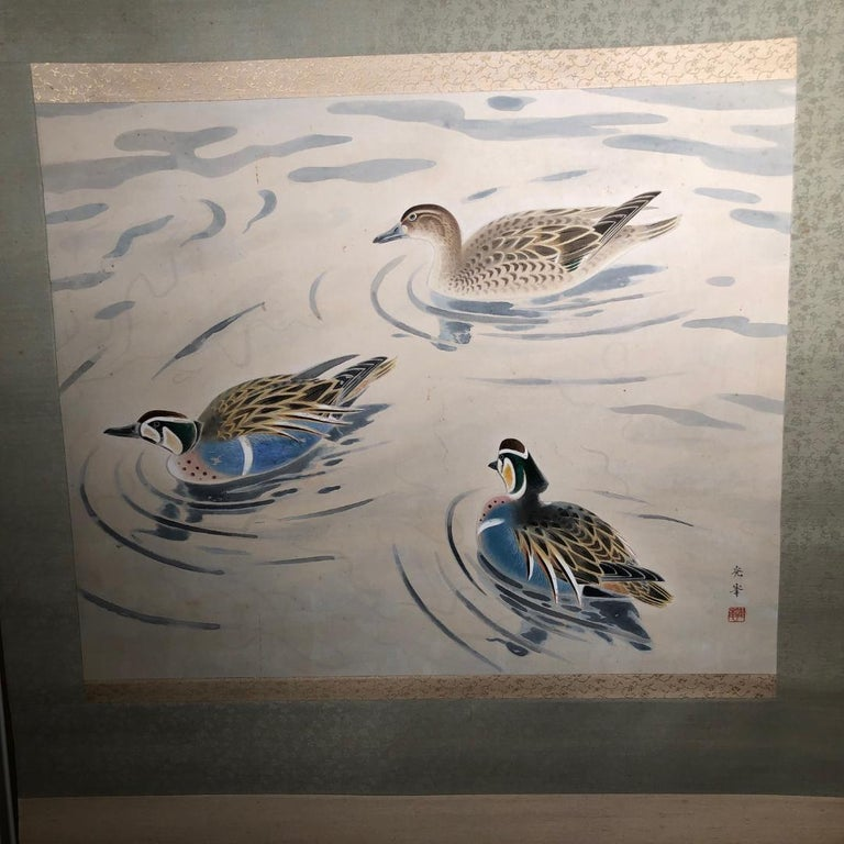 A very fine and bold Japanese antique hand painted silk scroll of three mandarin ducks in full vibrant plume.  Taisho period.  Hand painting in lively colors with great details, signed.  A signed wooden box tomobako accompanies.  Dimensions: