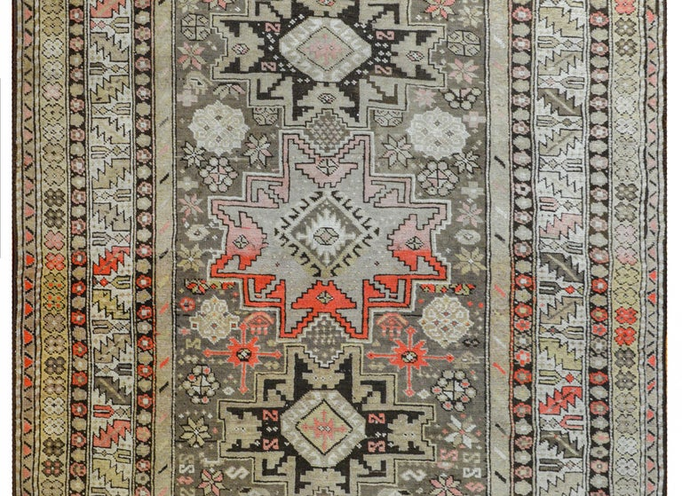 An extraordinary early 20th century Azerbaijani Shirvan rug three large stylized flower medallions amidst a field of more densely woven stylized flowers, all surrounded by myriad floral and geometric patterned stripes and all woven in abrash shades