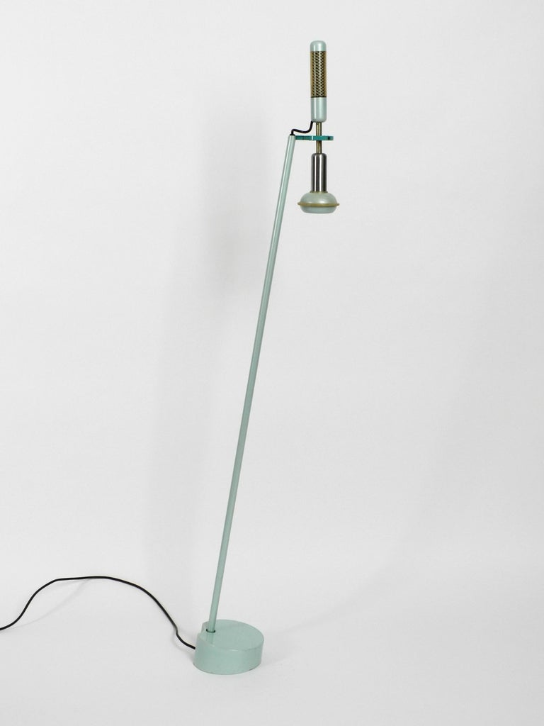 Stunning floor lamp by Achille and Pier Giacomo Castiglioni.  Manufactured by Flos in 1981. Beautiful in turquoise green. Made in Italy. Great minimalist Post Modern design from that time. Completely made of metal with a very heavy base for a