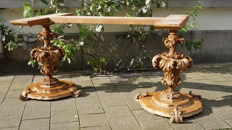 A extraordinary pair of table supports, in wood with layers of gold, and with deeply carved foliate leaves, on a ( later) base , with original wooden scrolls, also deeply carved and with the same layers of gold. Both pieces were part of an important
