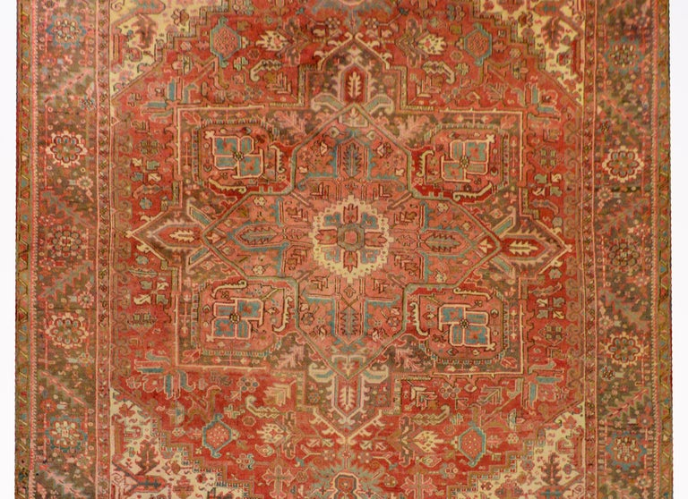 An extraordinary mid-20th century Persian Heriz rug with a large eight-sided floral patterned medallion on a field of flowers surrounded by a fantastic border woven with a large-scale floral and leaf pattern, all woven in crimson, orange, indigo,