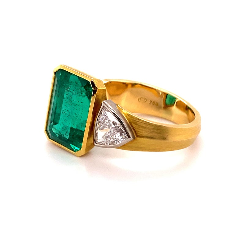 The ring is designed that the main stone is centered in between two fingers when worn. The bezel set, fine Colombian emerald of approximate 10.16 ct comes in an elegant longish step-cut. The gem is of a rich slightly bluish green colour with great