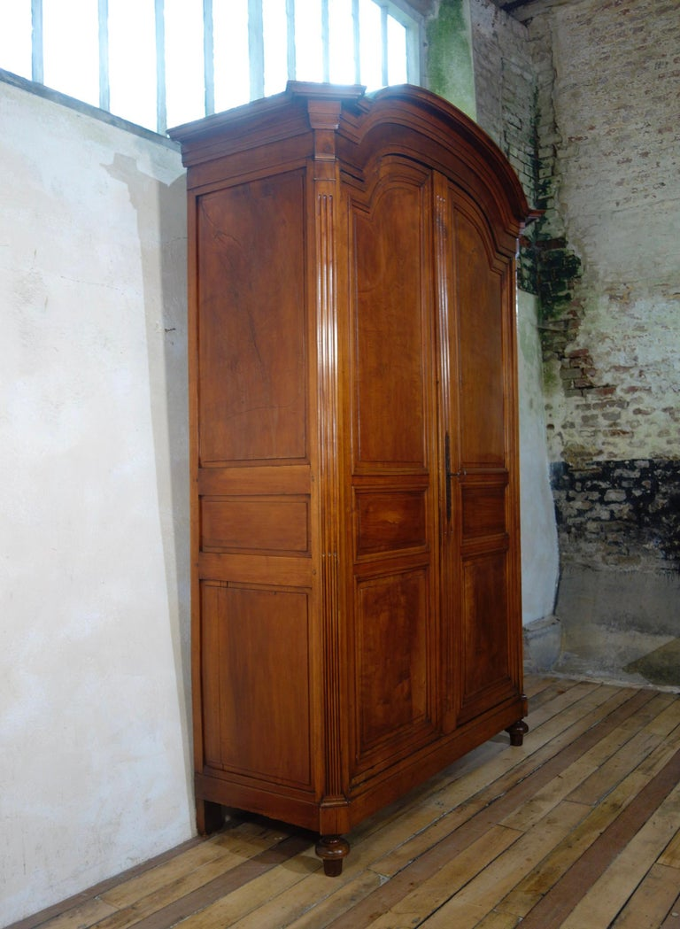 An extremely large Louis XVI walnut armoire, displaying a domed and molded cornice with projecting canted corners. This armoire demonstrates simple inset triple paneled doors, separated by a relief reeded pilaster. Each of the doors features